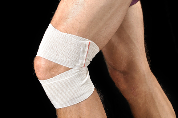 Closeup of man with sports wrap on knee as he runs on black background